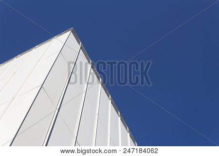 View Looking Up At Corner Of White Generic Building Facade Against A Very Deep Blue Sky, Horizontal