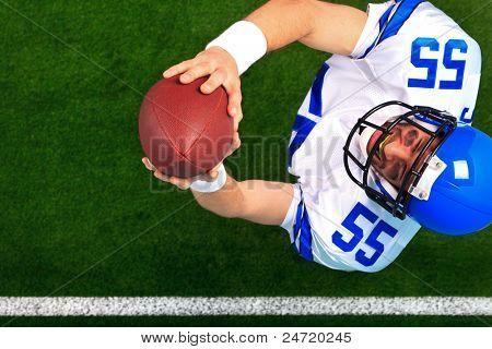 Obenliegende Foto des ein American-Football-Spieler Wide Receiver Fang den Ball in der Luft. Die unifor