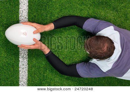 Foto aérea de um jogador de rugby mergulho sobre a linha para marcar um try com ambas as mãos segurando o bal