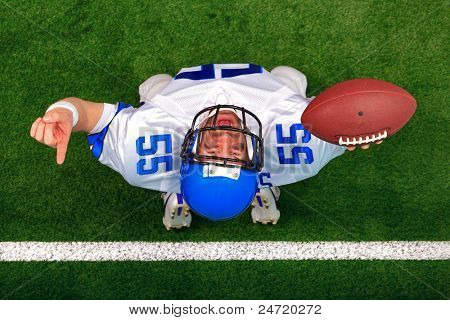 Overhead photo of an American football player making a touchdown celebration looking up in the air with his finger raised. The uniform he's wearing does not represent any actual team colours.
