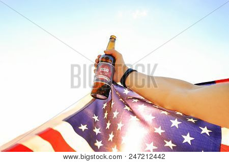 4Th Of July Celebration Party. Young Man Holding Brown Beer Bottle With Happy Independence Day Label