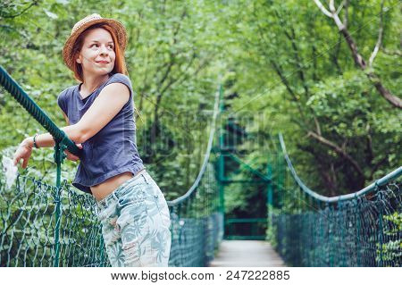 Young Woman In The Forest On The Wooden Bridge Enjoying Summer