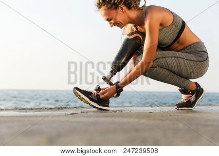 Smiling disabled athlete woman with prosthetic leg tying shoelace outdoor