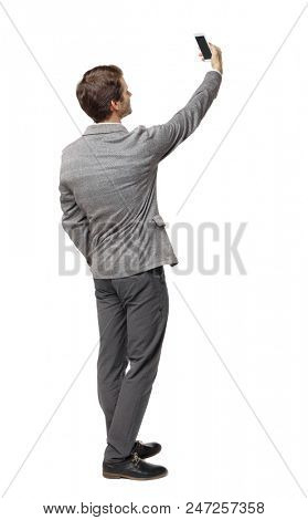 Back view of a businessman in a suit making a selfie. rear view people collection. Isolated over white background. backside view of person.  A guy makes a photo with a phone