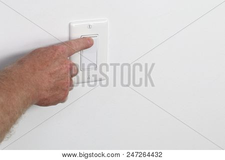 One Adult Male Hand Pressing A Light Switch Panel. One Flat White Panel Light Switch Being Turned On