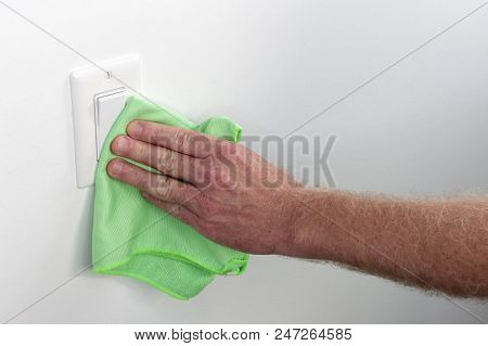 Persons Hand Wiping A Wall White Light Control. Inside White Wall Light Switch Cleaned With A Cloth.