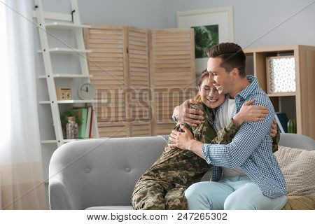 Woman In Military Uniform With Her Husband On Sofa At Home