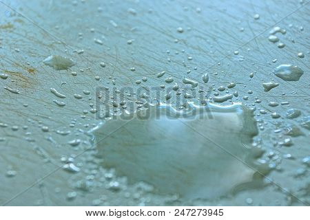 A Large Drop Of Water On A Gray Withered Table