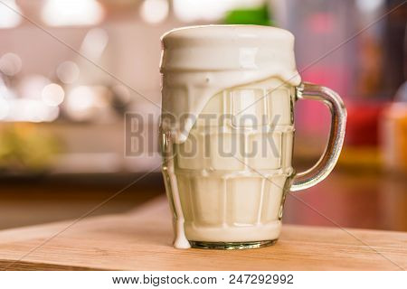 Closeup View Pouring Fresh Kefir Probiotik Drink Into Overfilled Clear Glass Cup On Kitchen Table.