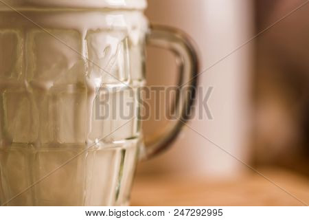 Closeup View Fresh Kefir Probiotik Drink Emerged From Overfilled Empty Glass On Kitchen Table.