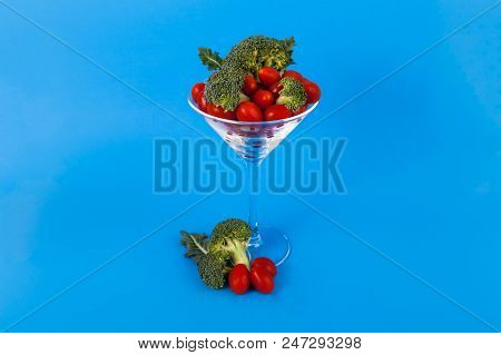 Martini Glass Filled With Sweet Cherry Tomotes Organic Broccolli Florets On A Blue Background
