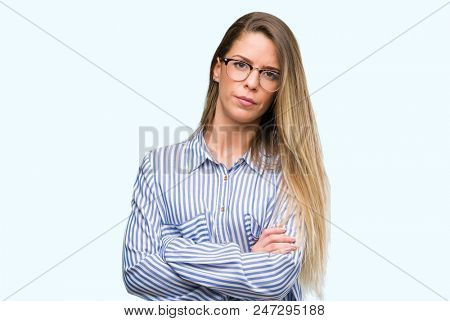 Beautiful young woman wearing elegant shirt and glasses skeptic and nervous, disapproving expression on face with crossed arms. Negative person. poster