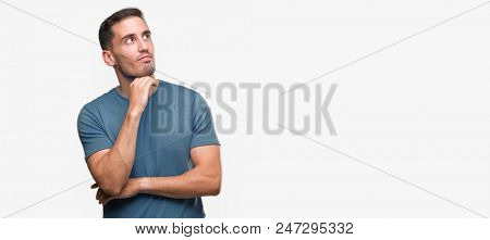 Handsome young casual man with hand on chin thinking about question, pensive expression. Smiling with thoughtful face. Doubt concept.