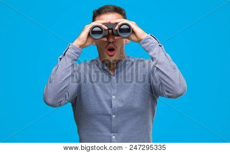 Handsome young man looking through binoculars scared in shock with a surprise face, afraid and excited with fear expression