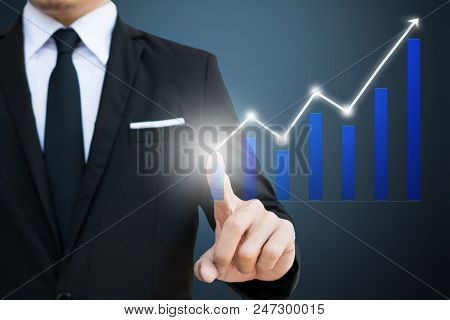 Businessman Touch On Vitual Screen With Financial Charts Showing Growing Revenue