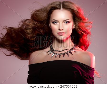 Woman high fashion model with luxurious long healthy wavy, voluminous hair in Colorful Bright Lights. Beautiful girl with chains necklace. Ledy in rock and roll style on colourful vivid red background