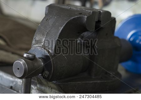 Vise tool on wooden top surface. Vise on workbench. Tool for metalworking. Engineer or blacksmith and industry instrument. Fixing and squeezing. poster