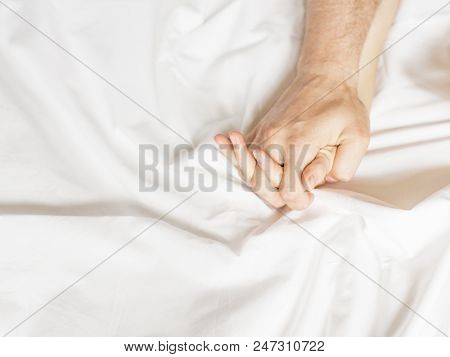 Sensual Beautiful Young Couple Is Having Sex On Bed. Female Hand Pulling White Sheets In Ecstasy, Or