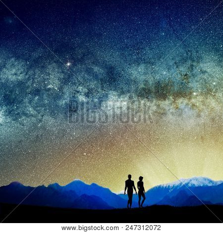 conceptual image of silhouetted people and abstract universe lights.