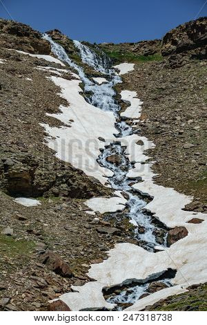 Waterfall With Ice And Snowfields In Mulhacen Mountain Peak Route