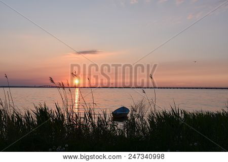 Sunset By The Swedish Olandbridge With Calm Water And A Rowing Boat In The Foreground