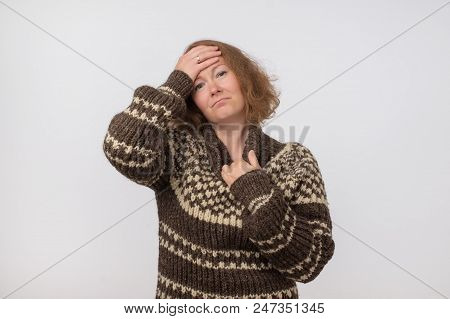 Portrait Of Sick Ill European Female Dressed In Big Wool Brown Sweater. Woman Suffering From Physica