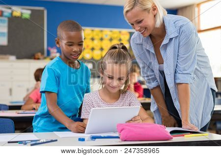 Multiethnic young students using digital tablet in classroom with teacher. Teacher in class with kids using electronic tablet. Teacher teaching how to use electronic device at elementary school.