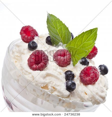 cream dessert with fresh berries : raspberry and blueberry on white