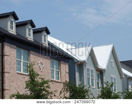 Dormers On Brick Structure Contrast With Neighboring Homes On This Street In A New Development Under