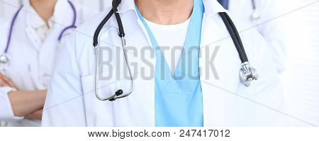Groupe Of Unknown Doctors Standing Straight In Hospital Office. Close Up Of Stethoscope At Practitio