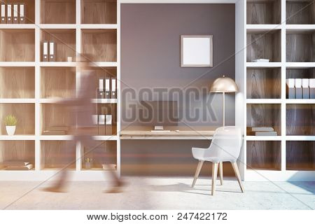 Businessman In A Gray Home Office Interior With A Concrete Floor, A Computer Table And Bookcases Wit