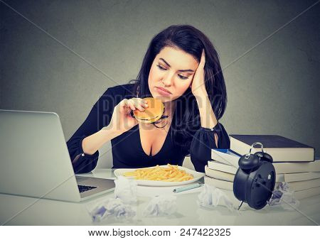 Sedentary Lifestyle And Junk Food Concept. Tired Stressed Woman Sitting At Her Desk Eating Hamburger
