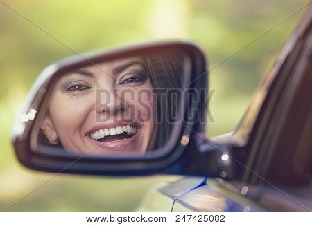 Happy Young Woman Driver Looking In Car Side View Mirror, Making Sure Lane Is Free Before Making A T