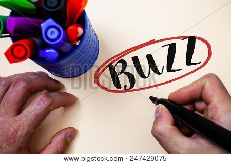 Conceptual hand writing showing Buzz. Business photo text Hum Murmur Drone Fizz Ring Sibilation Whir Alarm Beep Chime Man holding black marker markers table ideas message communicate poster