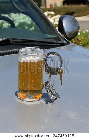 Drinking and Driving concept. DUI Concept. Beer Mug with Beer, Hand Cuffs and Car Keys. Driving while intoxicated concept.  poster
