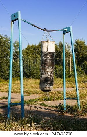 Old Punching Bag Hangs On A Bar On An Abandoned Sports Ground. The Concept Of A Healthy Lifestyle