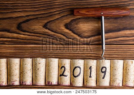 2019 New Year Background With Wine Corks And A Bottle Opener Or Corkscrew On A Textured Rustic Wood