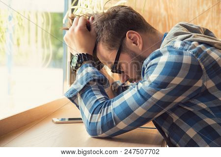 Young Depressed Man Sitting At Table With Mobile Phone In Cafe Looking Down Being Unhappy With Break