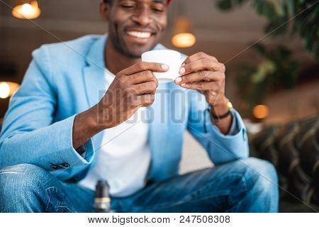 Positive Businessman With Brilliant Smile Resting While Tasting Mug Of Beverage. He Locating Indoor.