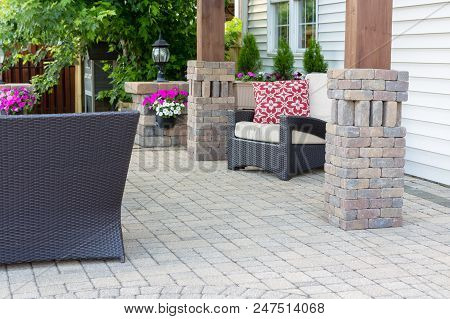 Elegant Wooden Pergola Legs With Ornamental Brick Cladding On A Paved Patio With Comfy Garden Furnit