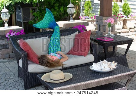 Young Girl Wearing A Blue Mermaid Tail Relaxing On A Sofa On A Patio Outdoors In The Shade As She Dr