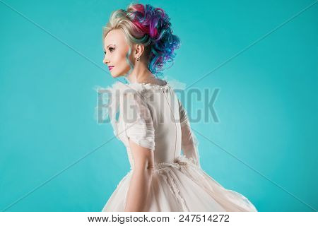 Beautiful Woman With Creative Hair Coloring. Stylish Hairstyle, Informal Style. Blue Background