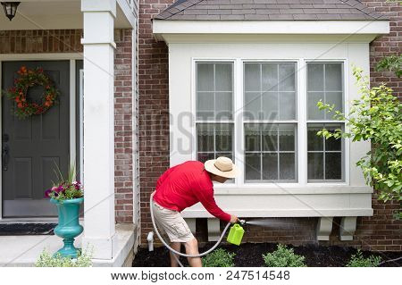 Man Cleaning The Underside Of A Bay Or Bump-out Window On An Upmarket Brick Home Using A Portable Ha