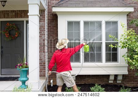 Man Spring Cleaning The Exterior Of His House Washing Down A Bay Window With A High Pressure Sprayer