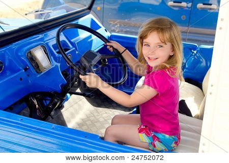 blond little smiling girl driving in retro blue convertible car