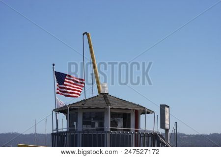 This Is An Image Of The Harbor Mater Building And U.s. Flag In Monterey, California
