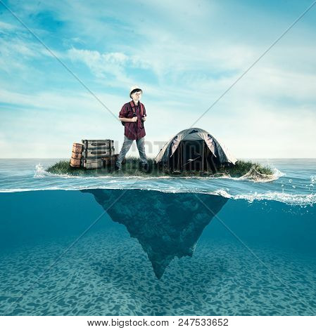 Traveler Kid On A Small Island With An Mounted Tent And Luggage In The Ocean. Split Half-water Seasc