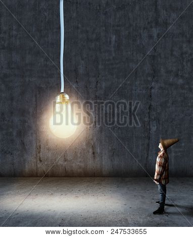 Kid Looking Up To A Lightbulb Hangs From Above In A Dark Room. The Concept Of A New Idea.