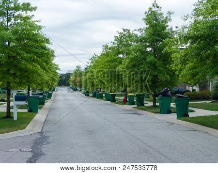 Tree Lined Urban Street With Dustbins Ready For The Garbage Collection On The Roadside On A Cloudy D