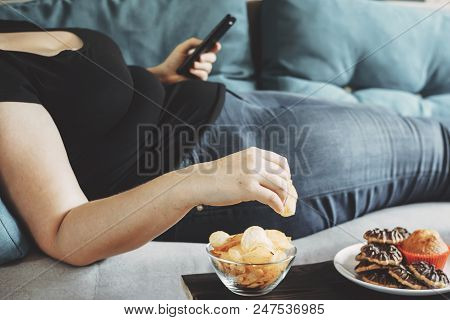 G, Sedentary Lifestyle, Compulsive Overeating. Obese Woman Laying On Sofa With Smartphone Eating Chi